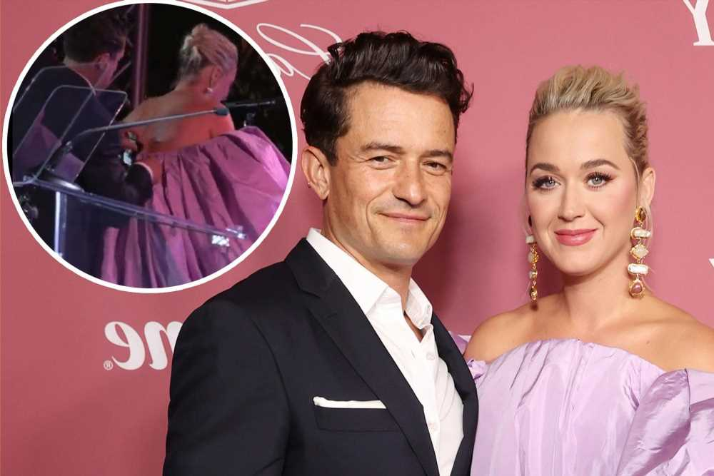 Orlando Bloom helps Katy Perry fix her dress at Power of Women event